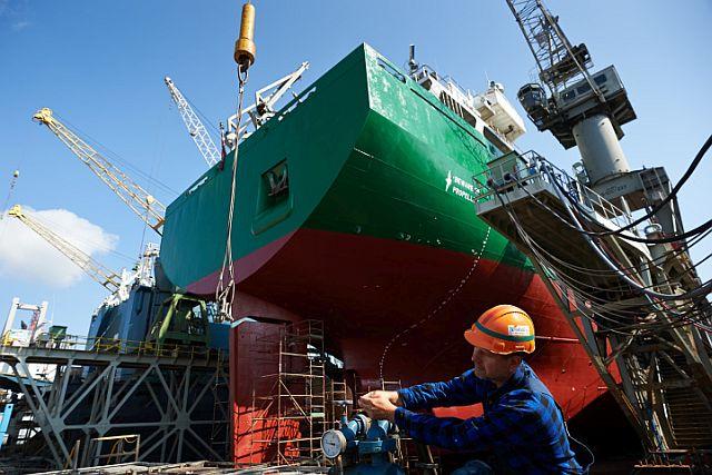 """Stocznia Remontowa """"Nauta"""" S.A. w Gdyni. Nz. pracownik obs³uguje pompê wodn¹ przy remontowanym statku w doku stoczni."""